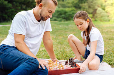 Little daughter playing chess with her father outdoors