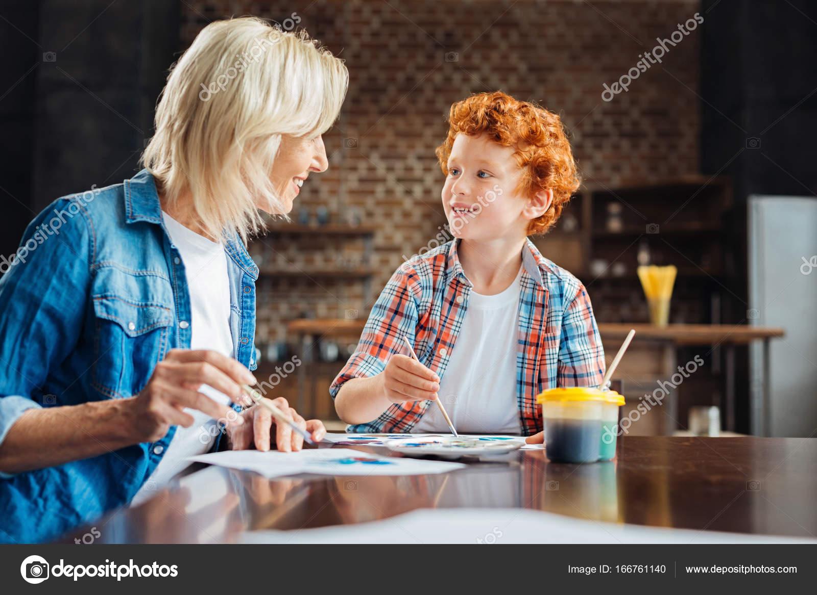 Niño emocionado hablando con la abuela mientras pinta — Fotos de ...