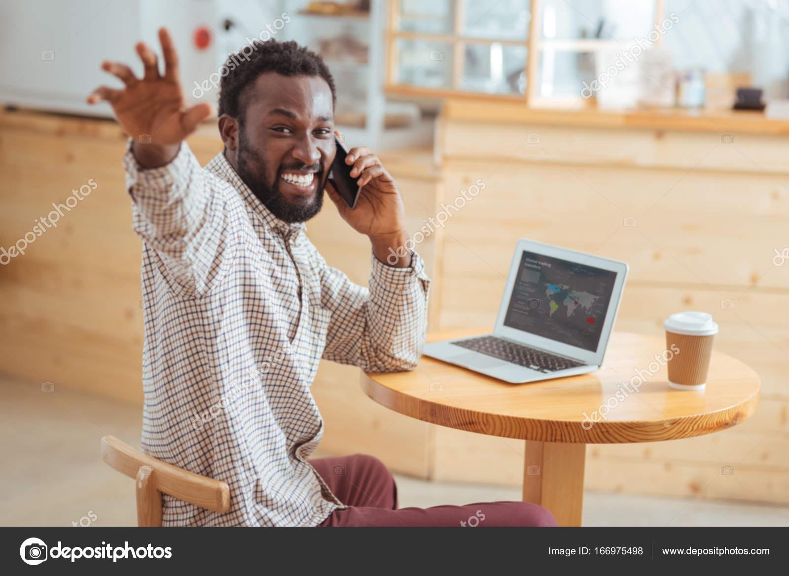 Overjoyed Man Greeting Someone While Talking On Phone Stock Photo