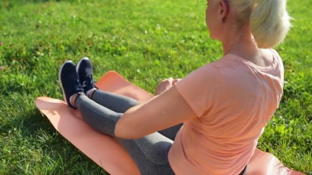 Žena, která dělá protahovací cvičení v parku