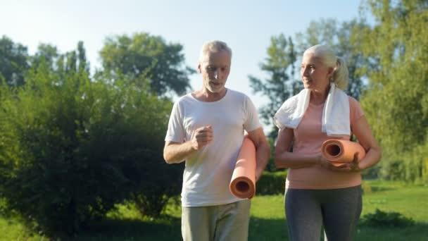 Paar spaziert mit Gymnastikmatten durch den Park