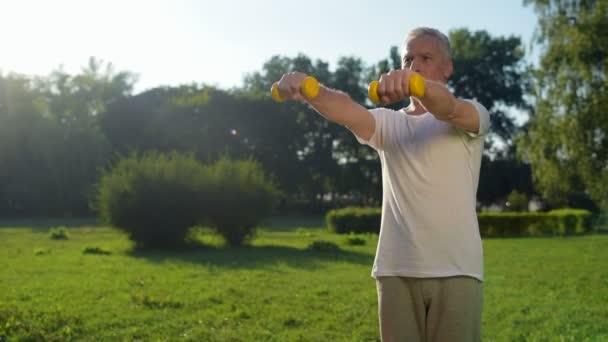 Mann übt mit den Hanteln im Park