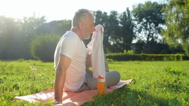 Mann ruht sich nach Sport-Übungen aus