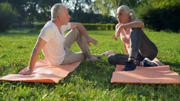 Paar sitzt auf den Gymnastikmatten
