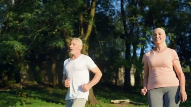 Überglückliches betagtes Paar joggt im Park
