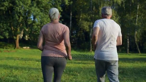 Pohled zezadu na pár starší sportovní běh v parku