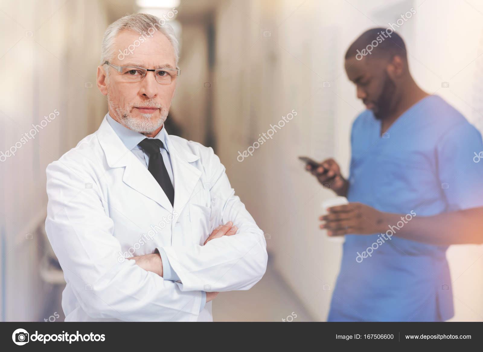 Hombre serio con pelos grises manteniendo los brazos cruzados en el ...