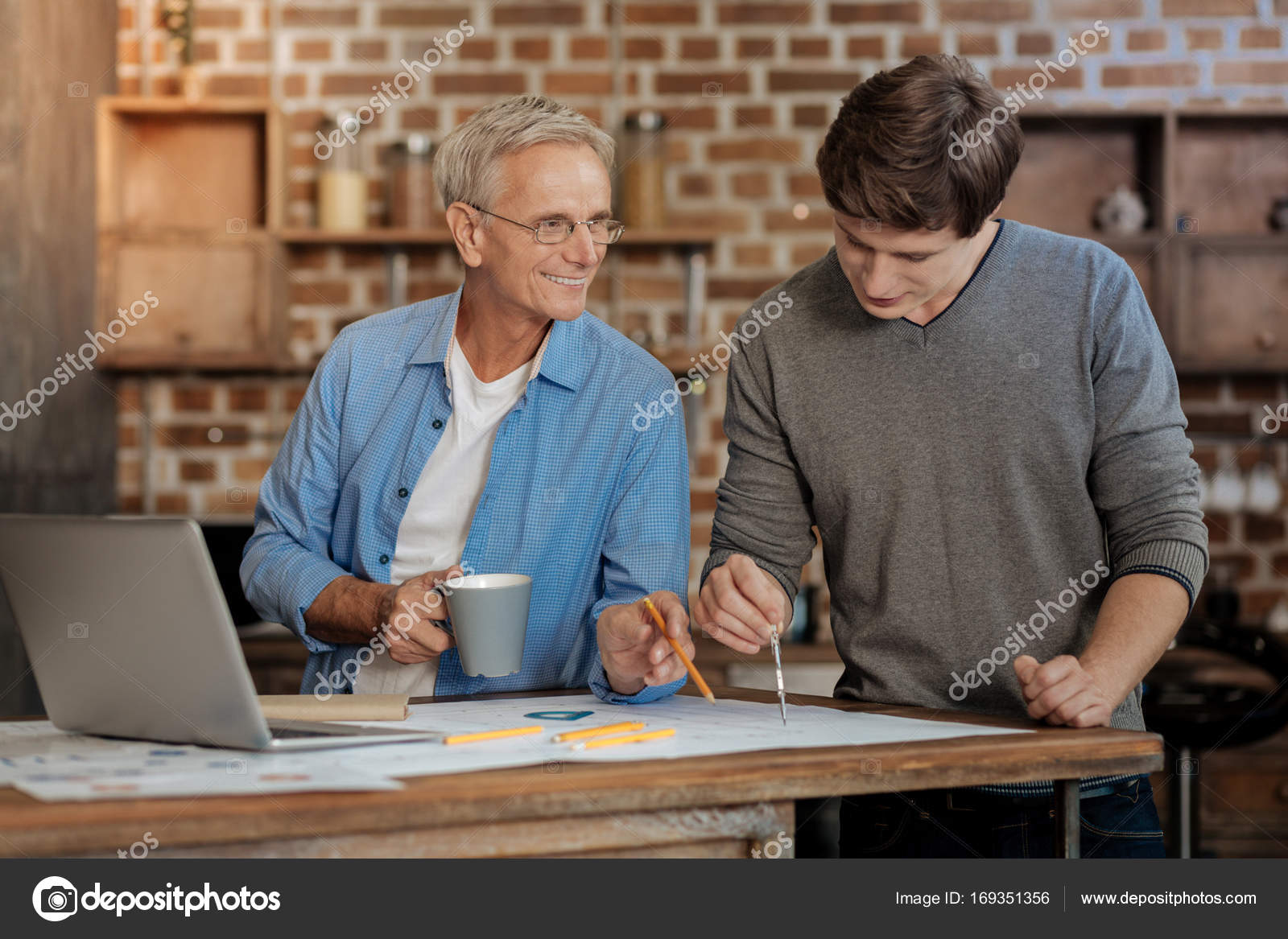 Pleasant mentor helping young colleague draw blueprint stock pleasant senior mentor holding a cup of coffee and helping his young colleague draw a blueprint by pointing at a place requiring correction photo by malvernweather Images