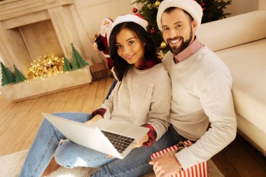 Lovely couple watching movie on laptop on Christmas