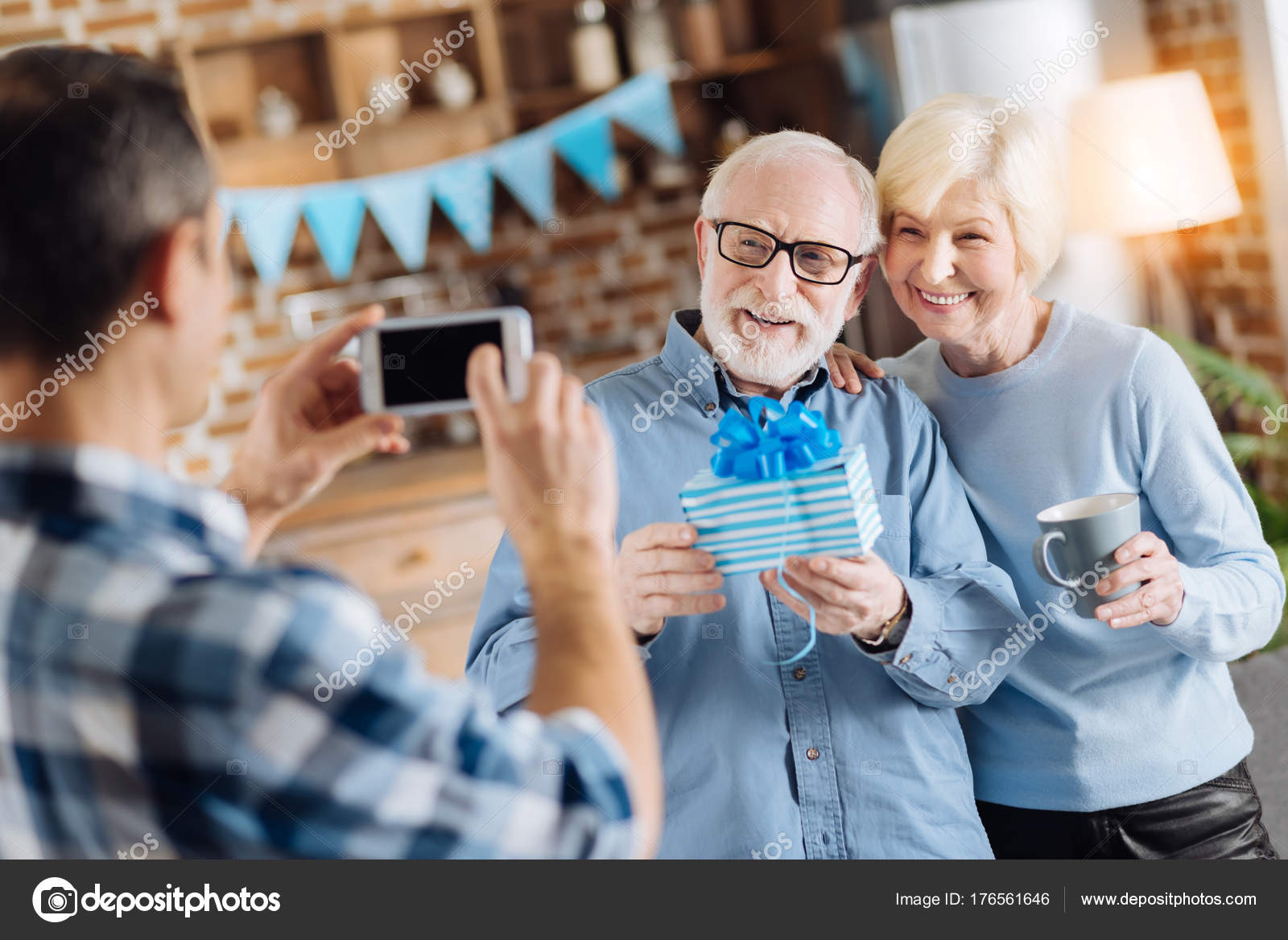 Loving Young Son Taking A Picture Of His Elderly Parents Posing With Birthday Present During The Party Photo By