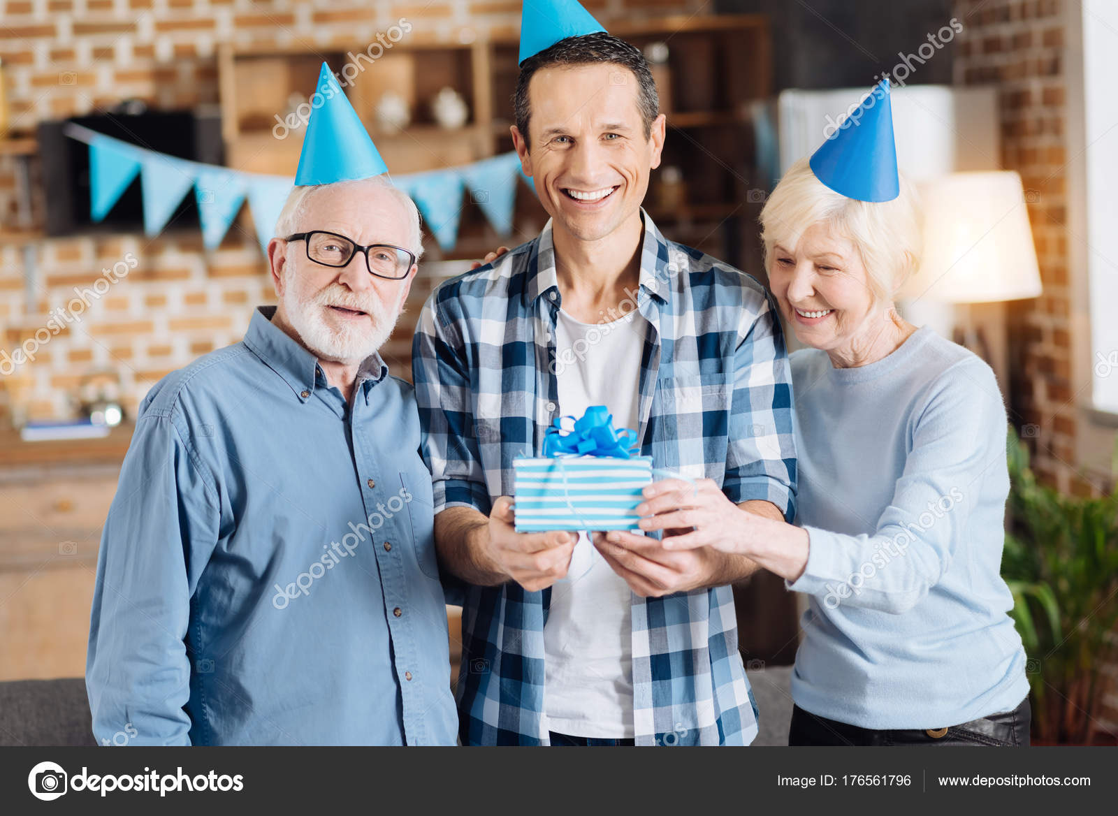 Upbeat Young Man Standing Between His Elderly Parents And Holding Birthday Gift While All Of Them Posing For The Camera Wearing Party Hats Photo