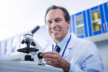 Delighted smart researches sitting in front of the microscope