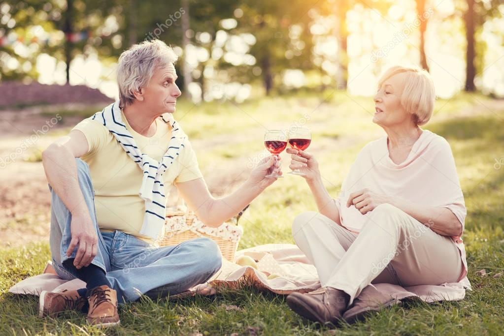 Delighted elderly couple drinking wine