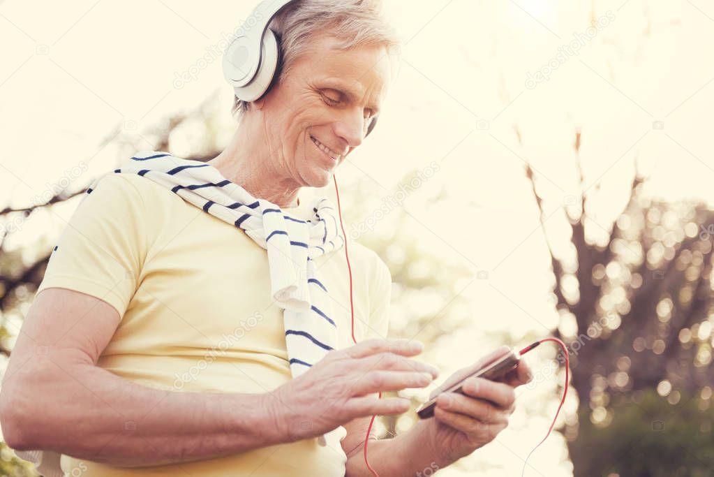 Joyful elderly man using an MP3 player