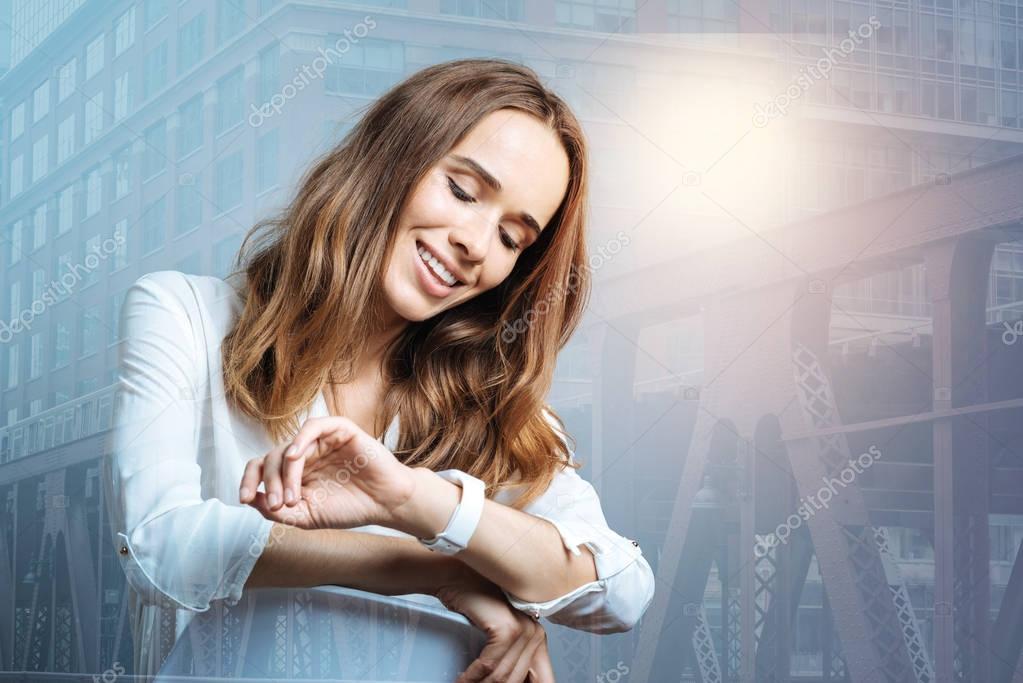 Joyful positive woman looking at her watch