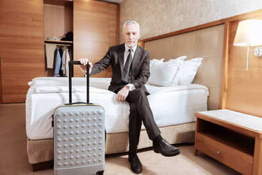 Senior glad man arriving at hotel