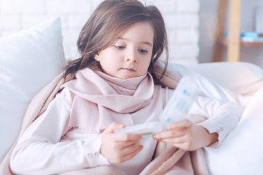Sad child looking attentively at medicine holder