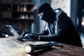 Taschenlampe auf dem Tisch liegend und Hacker im Hintergrund