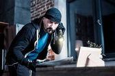 Konzentrierte bärtigen Dieb Diebstahl eines Laptops