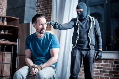 Masked criminal holding a pistol to mans head