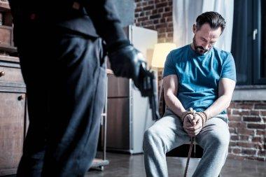 Unconscious man and a criminal standing near him