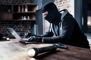 Masked computer hacker typing on the laptop