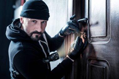 Skilful burglar unlocking the door