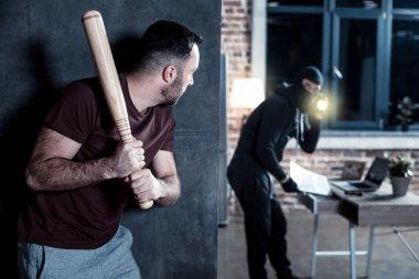 Intimidated man hiding from a burglar