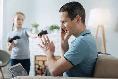 Busy man having no time on playing with daughter
