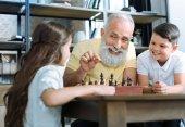 Fotografie Liebevolle senior Gentleman Lächeln während des Unterrichts Enkel Schach