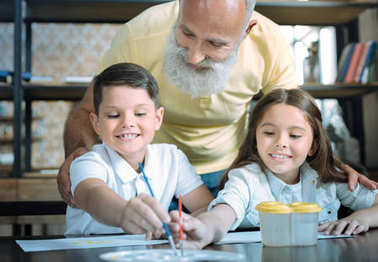 Careful grandfather looking at kids painting together