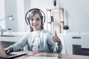 Satisfied young lady in headphones thumbing up for camera