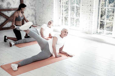 Beaming lady stretching leg and training