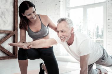 Enthusiastic senior man enjoying indoors workout