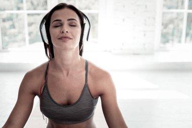 Joyful lady listening to music during meditation