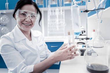Joyful female scientist smiling while holding test tubes