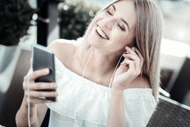 Joyful young woman listening to music