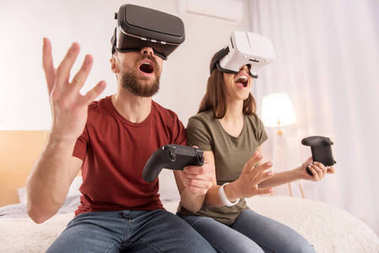 Funny vigorous couple gaming in VR glasses