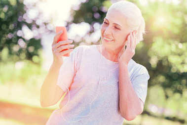 Delighted elderly woman using mobile phone