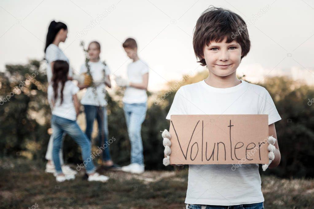 Cheerful nice boy being a volunteer