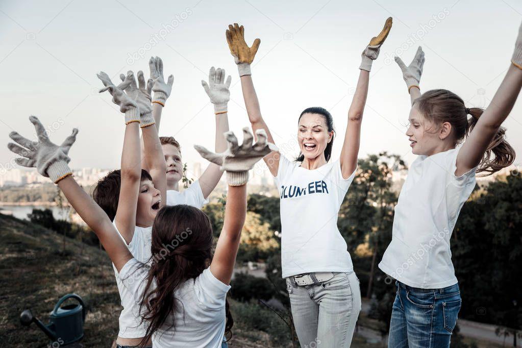 Happy joyful team raising their hands