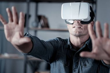 Is it real. Mature gentleman holding his arms in front while wearing a virtual reality goggles while playing computer game. stock vector