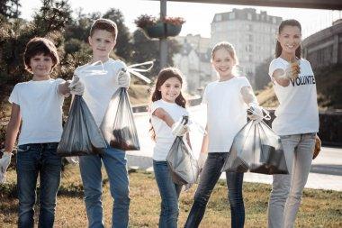Nice cheerful children holding litter bags