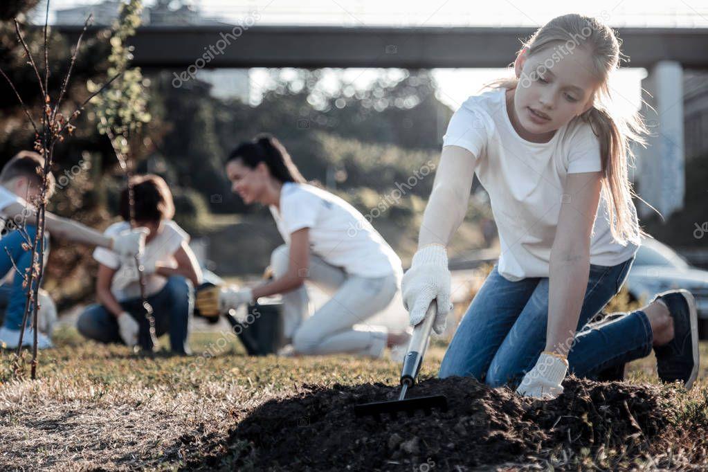 Pretty blonde girl working with a rake