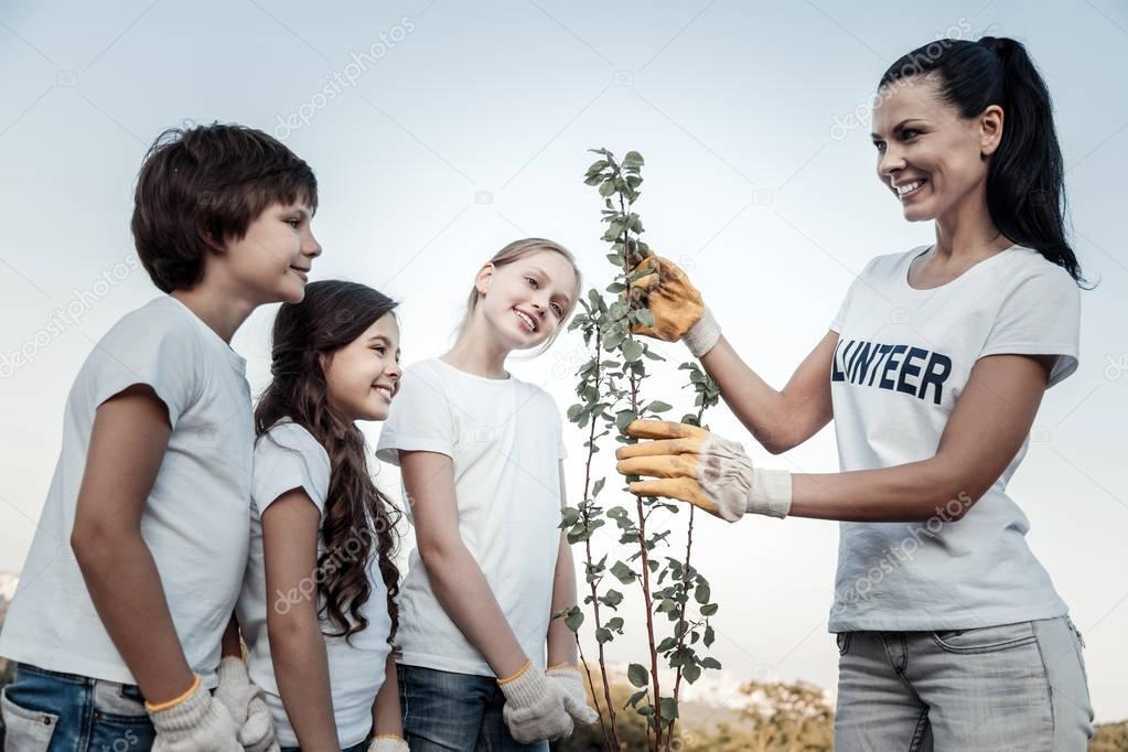 Joyful positive kids looking at the tree