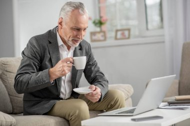 Concentrated man going to drink coffee