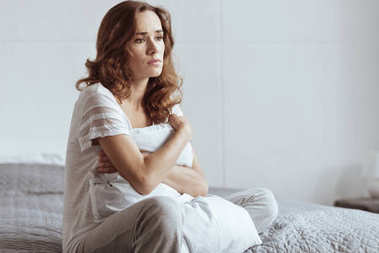 Depressed mature woman embracing pillow while sitting on bed
