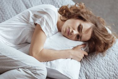 Nervous brunette lady embracing pillow and thinning about something depressing