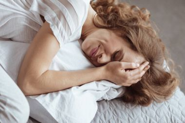 Emotionally exhausted woman crying on pillow