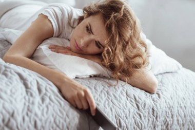 Depressed woman having negative thoughts while lying on bed
